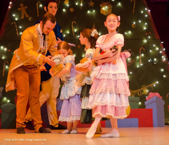 Lisa Kobayashi, (2pm) Clara holding the Nutcracker. Behind are Erik Sobbe (left) and Dalton Heinle (costumed as party guest parents)