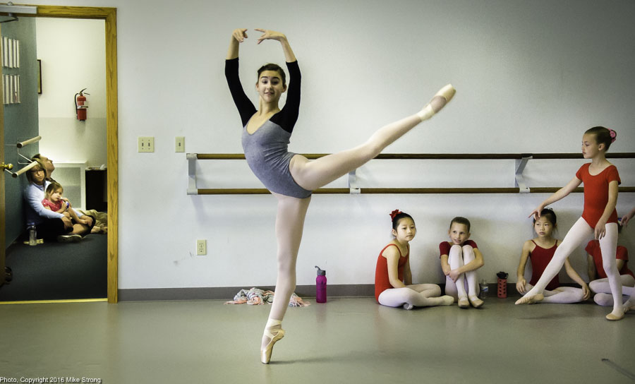 Studio Multiple Layers: Malerie Moore in a pique arabesque while behind her are parents in the hallway and younger dancers both sitting along the edges and going on.