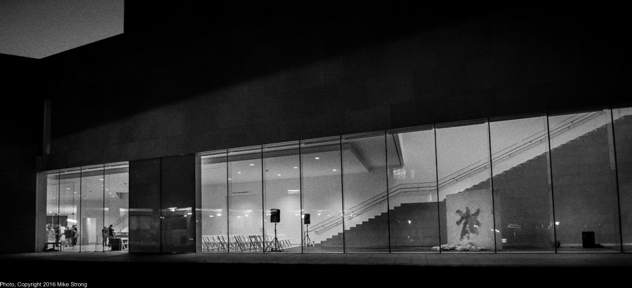 The Nerman after the performance of Relic by Jonah Bokaer with the after-reception crowd just showing in the left window and the audience space and set showing in the right window with the Relic standing in front of the stairs