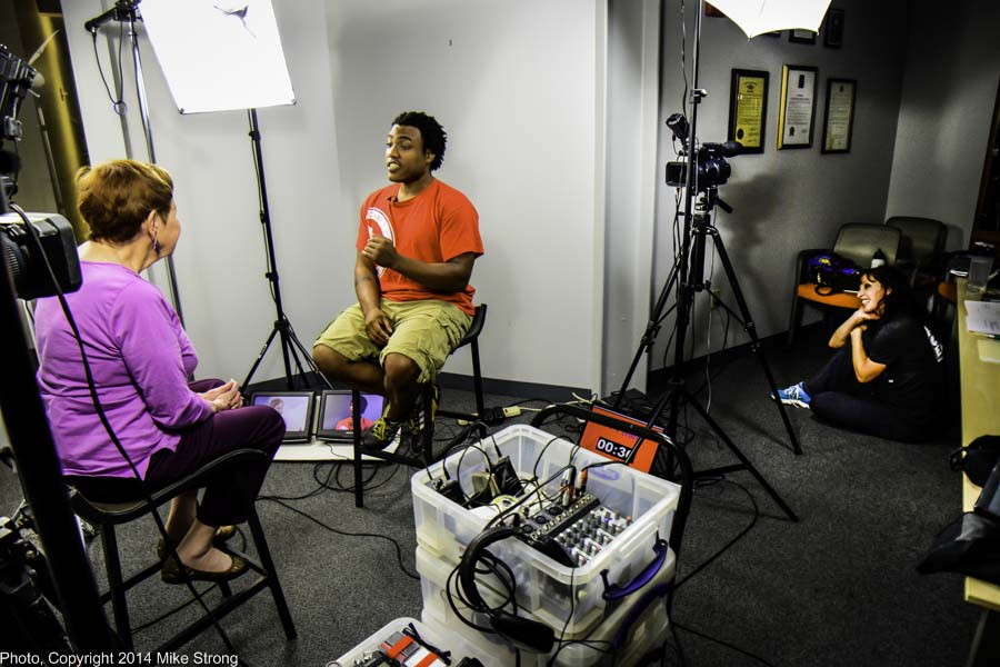 Billie interviewing Ronald Harvey (capoeira) with wife Sonia sitting on the floor to the right